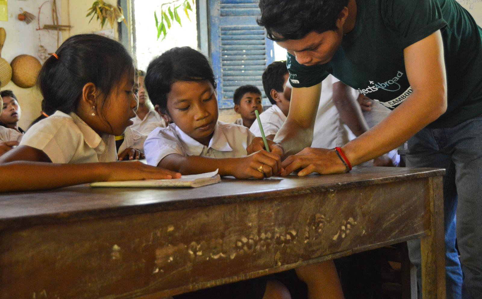 An international volunteer helps Cambodian children with their English homework
